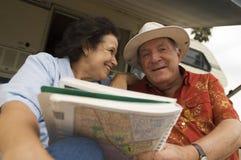 拿着地图书的资深夫妇 库存图片