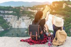拿着地图和旅行背包的妈妈和孩子战胜饰面坐教育自然的大峡谷 免版税库存图片