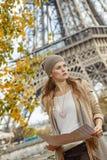 拿着地图和调查距离的端庄的妇女在巴黎 免版税库存图片