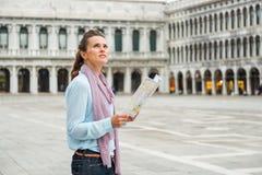 拿着地图的外形的妇女查寻在圣标记正方形 图库摄影