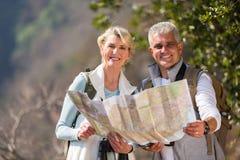 拿着地图的夫妇远足者 免版税库存照片