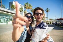 拿着地图的妇女显示某事对她男朋友笑 免版税图库摄影