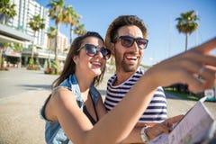 拿着地图的愉快的妇女显示某事对她的男朋友 图库摄影