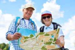 拿着地图的愉快的资深游人 库存照片