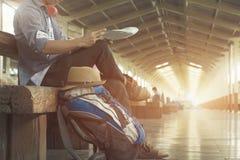 拿着地图的旅客佩带的背包,等待火车在火车站和飞行为下次旅行 免版税库存照片