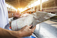 拿着地图的旅客,等待火车在火车站和飞行为下次旅行由移动电话 免版税库存图片