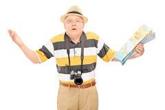 拿着地图的迷茫的成熟游人 免版税库存照片