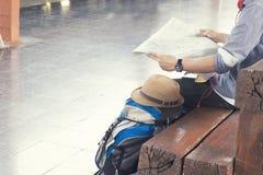 拿着地图,等待火车在火车站和飞行为下次旅行的旅客佩带的背包 免版税库存照片