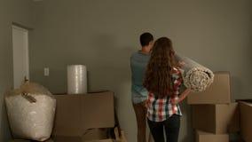 拿着地毯的愉快的年轻夫妇 影视素材