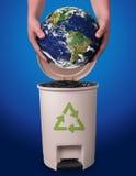 拿着地球上面的手被回收的容器 免版税库存照片