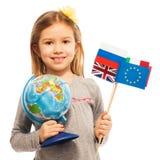 拿着地球和不同的旗子的女小学生 图库摄影