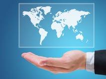 拿着地球地图的商人手被隔绝在蓝色背景 图库摄影