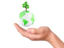 拿着地球地球和树在他的手上 库存照片