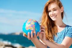 拿着地球的微笑的妇女在海 免版税图库摄影