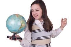 拿着地球的愉快的学校女孩 免版税库存照片