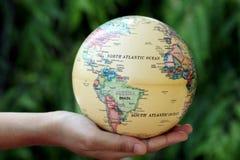 拿着地球的手反对绿色 库存图片
