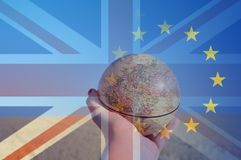 拿着地球的手的Brexit概念集中于领域的欧洲分层堆积与英国国旗和E U旗子 代表 图库摄影