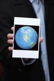 拿着地球的照片的商人在他的手上 库存图片
