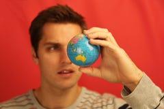 拿着地球的英俊的男性 库存图片