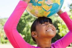 拿着地球的逗人喜爱的小女孩 免版税图库摄影
