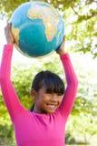 拿着地球的逗人喜爱的小女孩 免版税库存照片