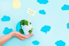 拿着地球纸和绿色新芽拼贴画的女性手塑造与它` s我们的在蓝色背景的家庭尖与纸太阳和 库存照片