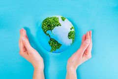 拿着地球纸和绿色新芽拼贴画的顶视图女性手在蓝色背景塑造 地球在您的手上,保存的地球co 免版税库存照片