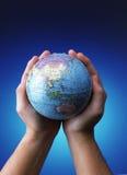 拿着地球(亚洲地区)的手 免版税库存照片