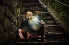 拿着地球Planetin的孩子秘密 图库摄影