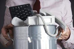 拿着垃圾箱用过时办公设备的商人 免版税库存照片