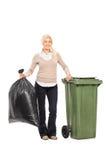 拿着垃圾袋的妇女在垃圾桶旁边 免版税库存照片