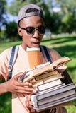 拿着堆与纸杯的书的盖帽和太阳镜的非裔美国人的人 免版税图库摄影