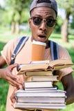 拿着堆与纸杯的书的盖帽和太阳镜的非裔美国人的人 库存照片