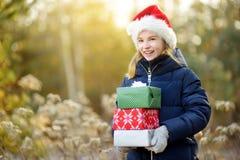 拿着堆圣诞节礼物的可爱的小女孩在美好的晴朗的冬日 免版税图库摄影