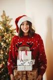 拿着堆礼物盒的圣诞老人帽子的愉快的少妇在gol 库存图片