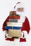 拿着堆礼物被包裹的礼物的圣诞老人 库存照片