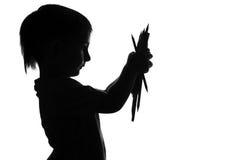 拿着堆色的铅笔的一个小男孩的剪影在手上 库存照片