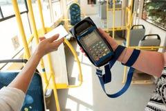 拿着塑料卡片的人的手 乘客支付在公共交通工具的车费 付款终端,信用卡读者,销售概念 免版税库存图片