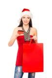 拿着塑料卡片的圣诞节帽子的一个少妇 免版税库存照片