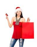 拿着塑料卡片的圣诞节帽子的一个少妇 库存照片