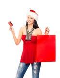 拿着塑料卡片的圣诞节帽子的一个少妇 库存图片