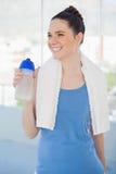 拿着塑料烧瓶和体育毛巾的微笑的苗条妇女 免版税图库摄影