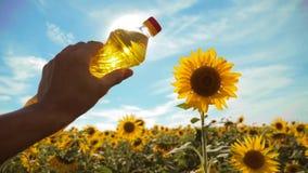 拿着塑料瓶向日葵油的农夫在他的手领域阳光下 慢动作录影 蓝色生活方式天空 股票视频
