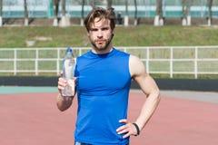 拿着塑料瓶饮用水的运动员人 免版税图库摄影