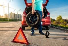 拿着备用轮胎的人反对残破的汽车 库存照片