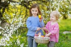 拿着复活节彩蛋的篮子两个小女孩 免版税库存照片