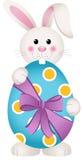拿着复活节彩蛋的逗人喜爱的兔宝宝 免版税库存图片