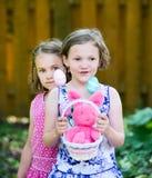 拿着复活节篮子用鸡蛋和兔宝宝的女孩 库存照片