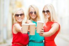 拿着外带的咖啡杯的Blonds在城市 免版税库存照片