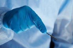 拿着外科解剖刀的外科医生手 库存图片